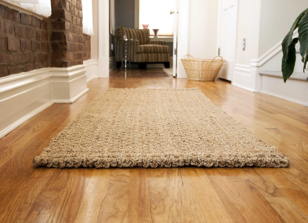 These features must ensure safety of a hardwood floor under the rug.