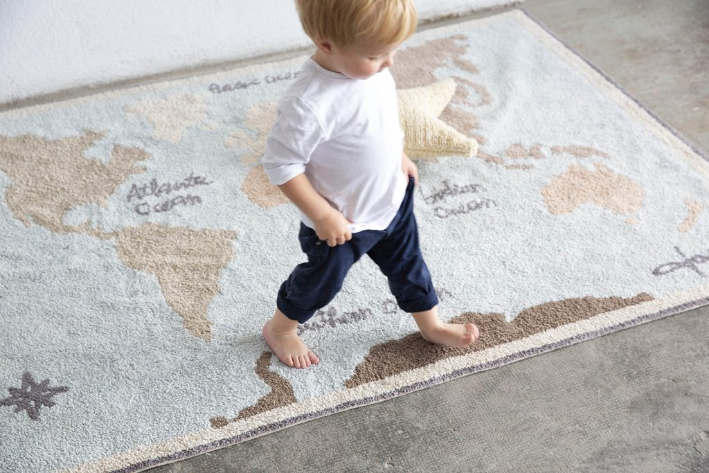Baby walking on a rug.