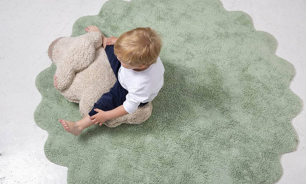 Baby sitting on a organic rug.